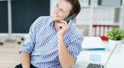 Bild Mann telefonierend an Laptop