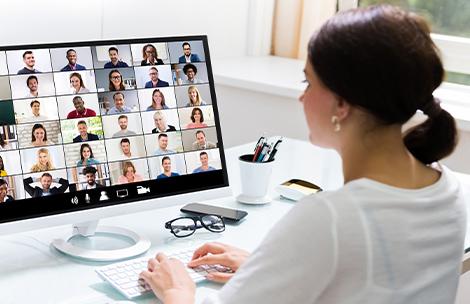 Frau vor Bildschirm im Home-Office kommuniziert mit vielen Menschen per Videokonferenz